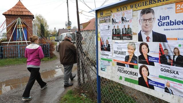 Zwei Personen laufen an Wahlplakaten vorbei