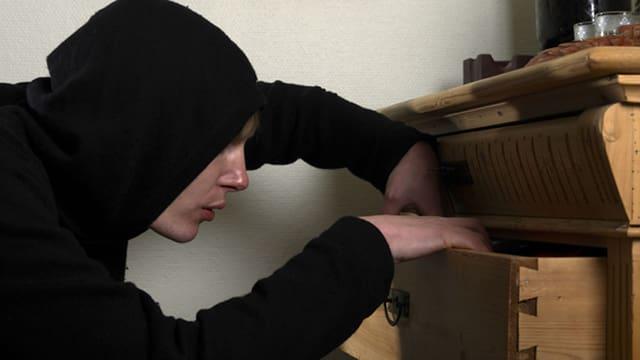 Einbrecher durchwühlt Schubladen