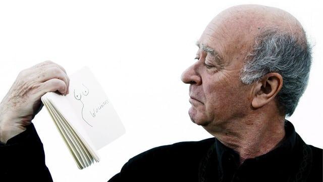 Wolinski schaut sich eine Zeichnung von ihm an.