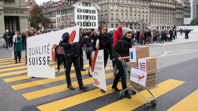 Unterstützer der Konzernverantwortungsinitiative gehen mit Einkaufswagen über einen Zebrastreifen.
