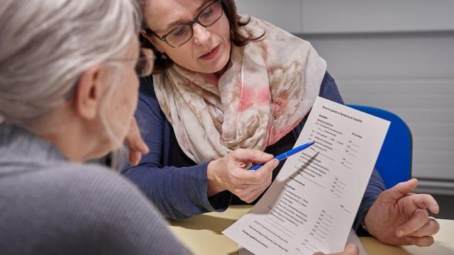 Eine Beraterin spricht mit einer älteren Frau. Sie schauen sich ein Dokument an. Die Beraterin zeigt mit einem Stift auf das Blatt.