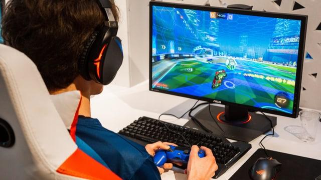 Ein junger Herr sitzt am Computer und spielt Rocket League.