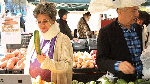 Frau prüft Gurke am Marktstand