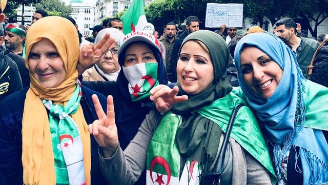 Vier Frauen mit Kopftuch und Algerien-Flagge auf der Strasse.
