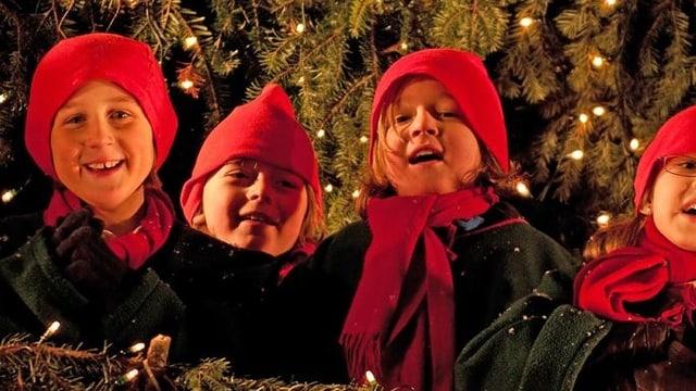Leuchtende Kinderaugen. Die kleinen Sänger sind ganz in ihrem Element. Mit ihren roten Mützen schmücken sie den überdimensionalen Weihnachtsbaum.