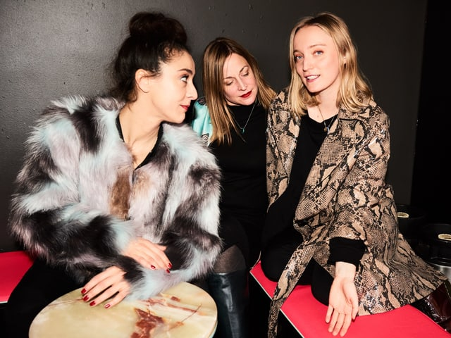 Drei Frauen in auffälligen Jacken.
