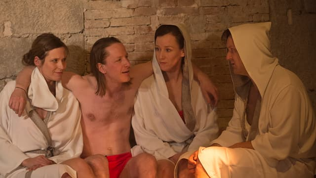 Zwei Männer und zwei Frauen sitzen in der Sauna.