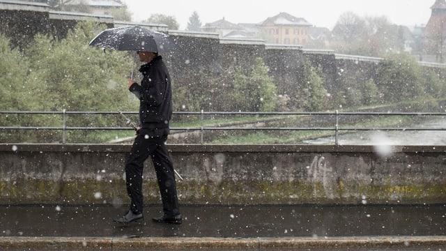 Ein Bürger mit dem als Stimmrechtsausweis geltenden Seitengewehr begibt sich zur Landsgemeinde. In der Hand einen Schirm, denn es schneit in Appenzell (AI). (keystone)