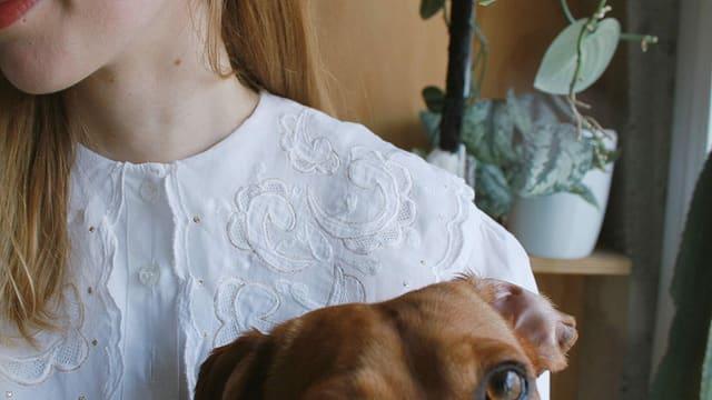 Detailansicht einer jungen Frau mit Hund im Arm.