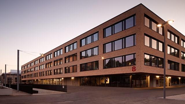 Ein Gebäude mit Flachdach mit brauner Verschalung.