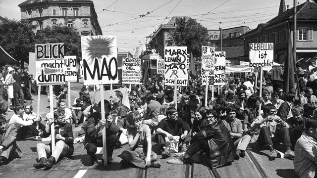 Junge Hippies sitzen auf der Strasse mit Schildern in der Hand.