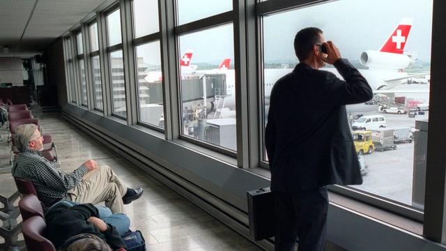 Geschäftsmann blickt am Flughafen Zürich telefonierend auf abtgestellte Swiss-Flugzeuge