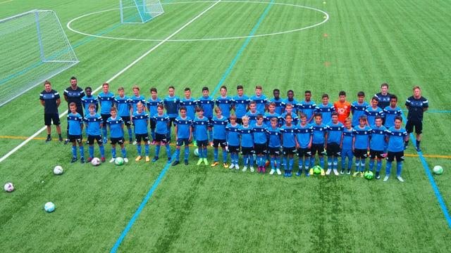 Ein Mannschaftsfoto mit 40 Juniorenfussballern und vier Trainern. Alle aufgereiht in zwei Linien hintereinander.