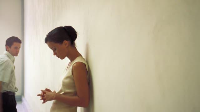 Frau lehnt mit gesenktem Kopf an der Wand.