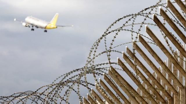 Flugzeug beim Starten, darunter ein Stacheldrahtzaun.