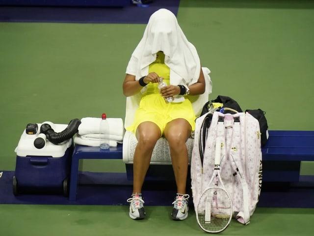 Naomi Osaka vergräbt sich auf dem Court unter einem Handtuch.