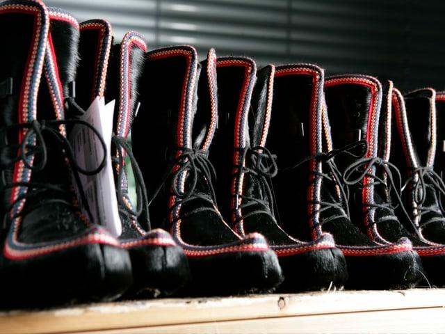 Eine Reihe von schwarz-roten Halbstiefeln.