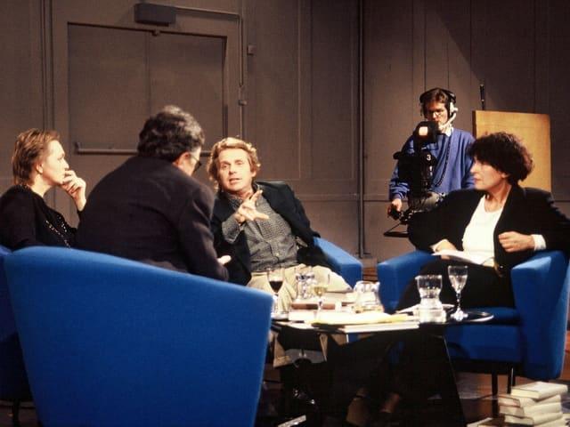 Vier Menschen sitzen auf Sesseln und diskutieren.