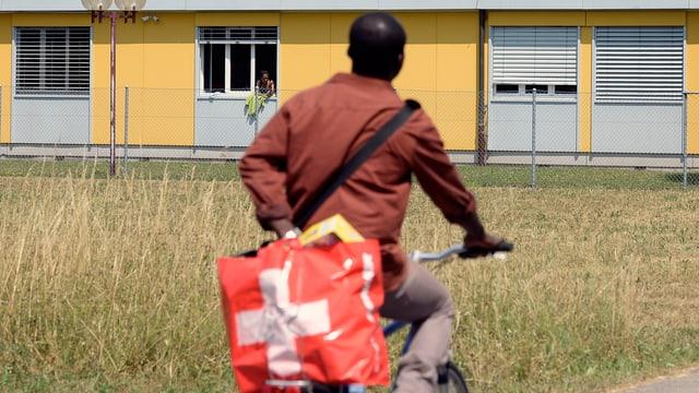 Ein Asylsuchender mit einer Einkaufstasche mit Schweizerkreuz.