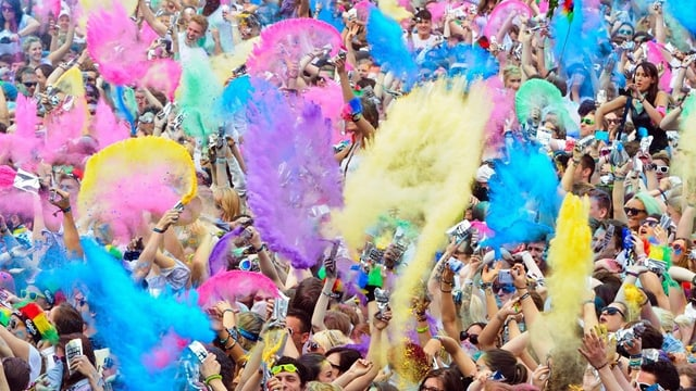 In einer Menschenmenge werfen die Leute gelbe, viollete, rosa, gelbe und blaue Pulver in die Luft.