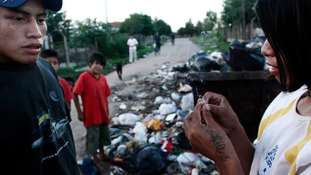 Zwei Jugendliche stehen auf einer verdreckten Strasse. Einer der beiden hält eine Paco-Zigarette in Händen.
