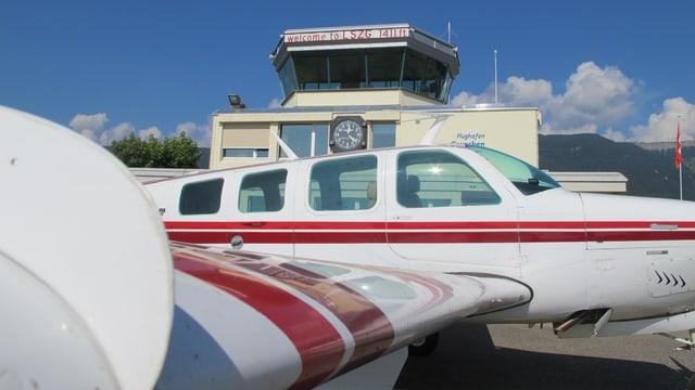 Flugzeug vor dem Tower des Flughafens Grenchen.