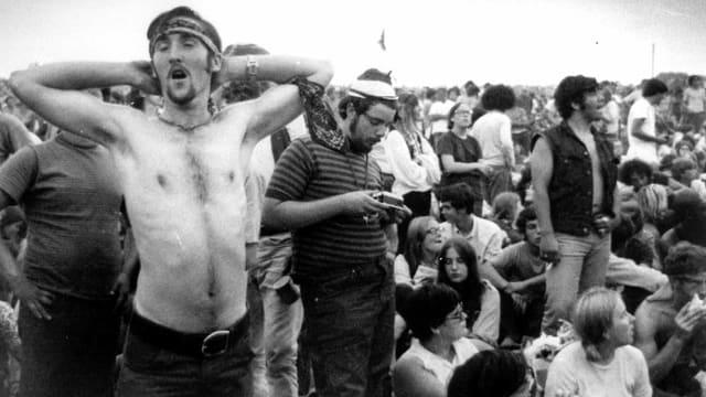 Junger Mann ohne Shirt steht in einer Menschenmenge und streckt sich