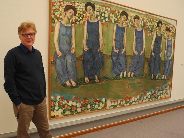 Ein Mann steht neben einem grossen Bild.