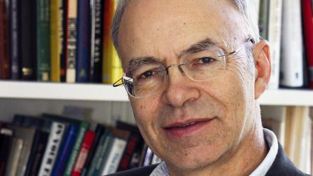 Peter Singer vor Bücherwand.