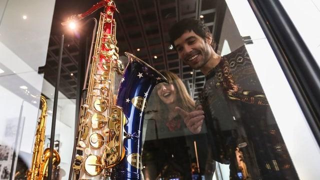Besucher einer Saxofon-Ausstellung bewundern Exponate