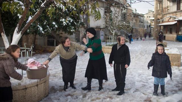 Frauen und Kinder stehen im Schnee und lachen.