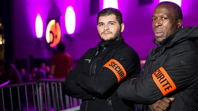 Zwei Männer mit verschränkten Armen, sie tragen eine orange Armbinde.