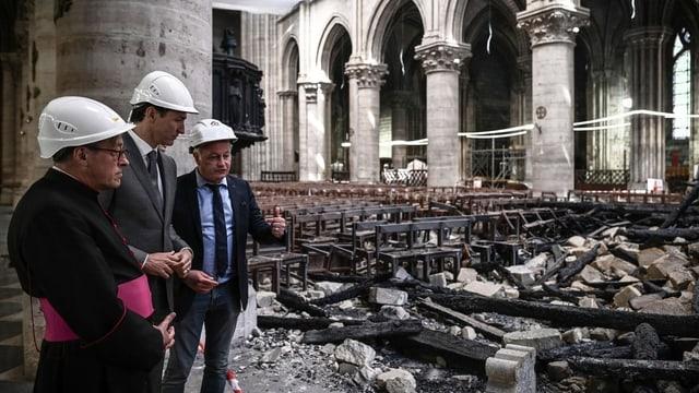 Drei Männer mit weissen Helmen stehen in einem zerstörten Kirchenschiff.