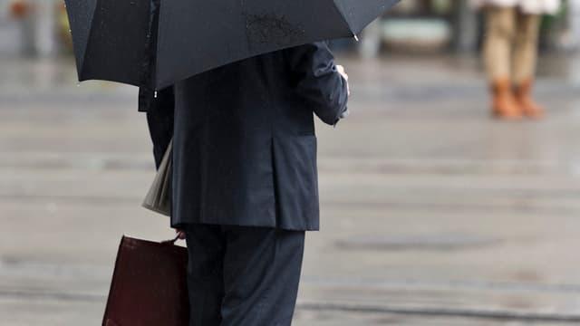 Banker in Zürich mit Schirm.