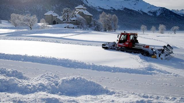 Pistenfahrzeug in verschneiter Landschaft.