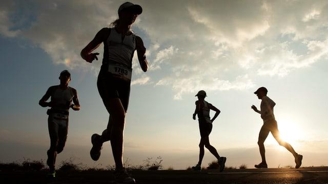 Vier Ironman-Teilnehmende während dem Marathon in der Dämmerung