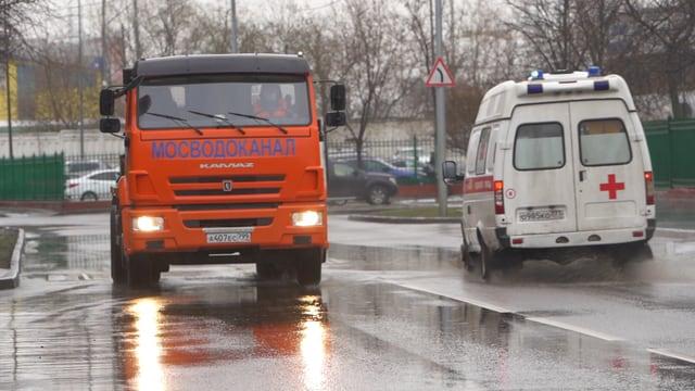 Ein Lastwagen der Moskauerabwasserbehörden links im Bild kommt einem Krankenwagen entgegen.