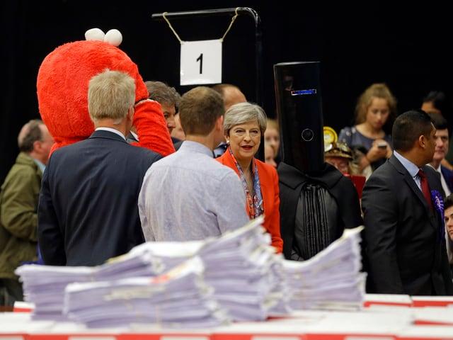 Theresa May im Wahllokal flankiert von den verkleideten Männern Lord Buckethead und Elmo