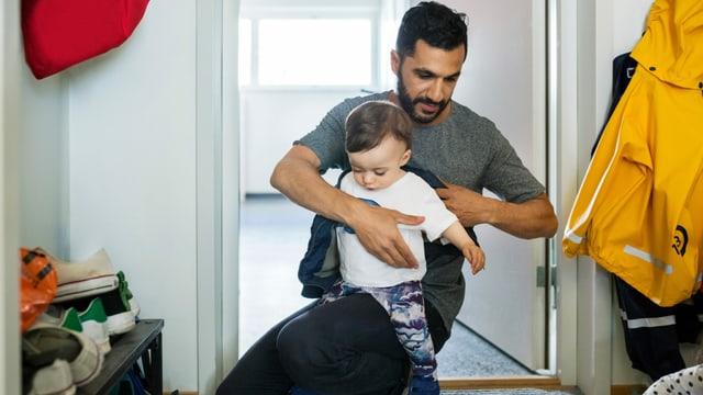 ein Mann zieht seinem Sohn eine Jacke an