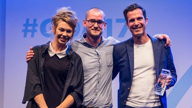 Drei Personen posieren lachend auf einer Bühne.