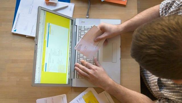 Mann von oben beim Online-Banking mit einem EInzahlungsschein an einem Mac-Computer.