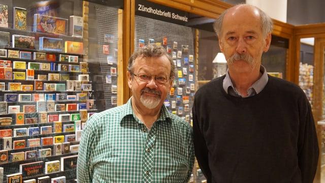 Zwei Männer posieren vor den Vitrinen ihrer Austellung.