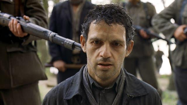 Mann bekommt ein Gewehr von hinten an den Kopf gehalten.
