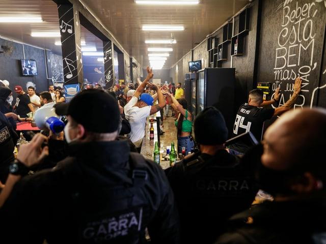 Feiernde und Polizisten in einer Bar