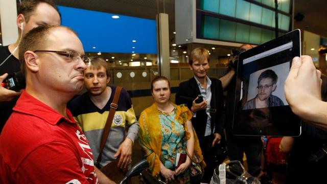 Journalist zeigt Fluggästen auf eine iPad ein Bild von Edward Snowden.