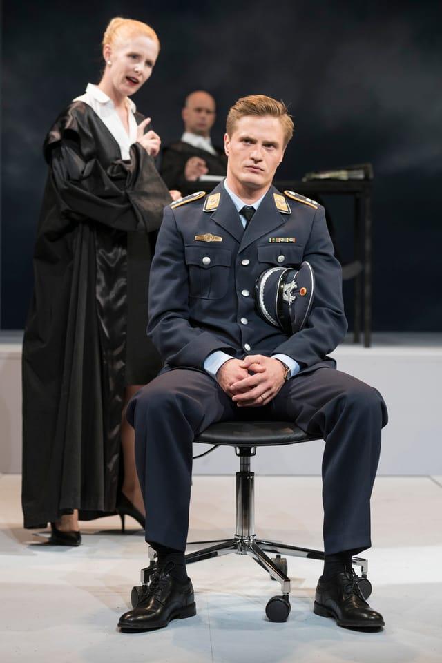 Ein Mann in Pilotenuniform sitzt auf der Bühne.