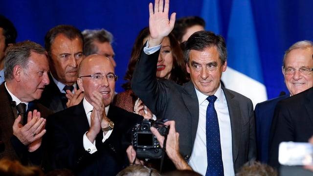 François Fillon hebt zum Dank die Hand, umringt von seinen Anhängern