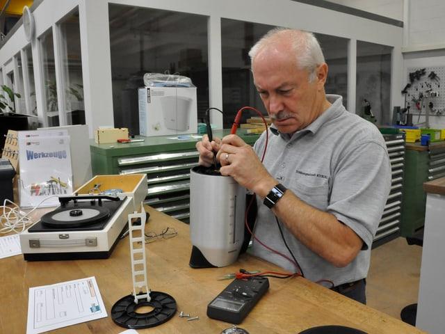 Ein Mann prüft mit zwei Elektroden einen Wasserkocher