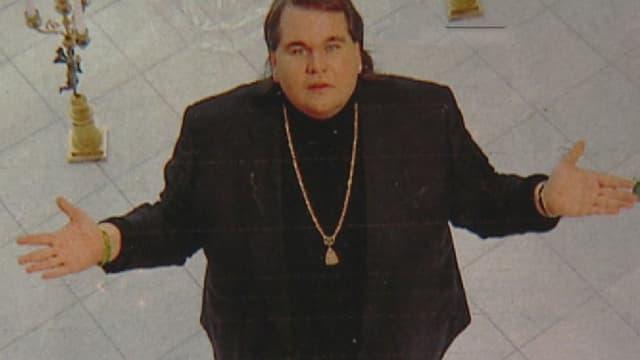 Ein übergewichtiger Mann mit goldenem Amulett steht mit ausgebreiteten Armen da und schaut nach oben in die Kamera.