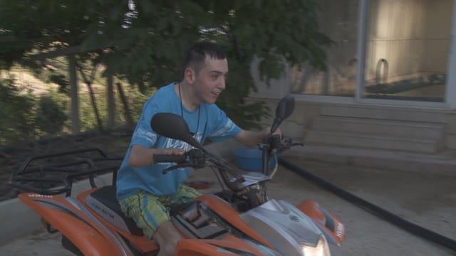 Yasin sitzt auf dem Motorrad.